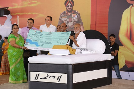 Smt. Laxmiben V. Patel (left) and Shree.Vallabhbhai Patel offering cheque to MorariBapu during the Ramkatha organized by Maruti Veer JawanTrust for the Families of Indian Soldiers