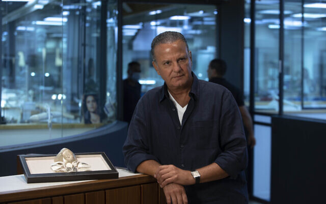 Isaac Levy, owner of Israeli jewelry company Yvel, speaks during an interview with The Associated Press, next to parts of a mask, in Motza near Jerusalem, August 9, 2020. (AP Photo/Sebastian Scheiner)